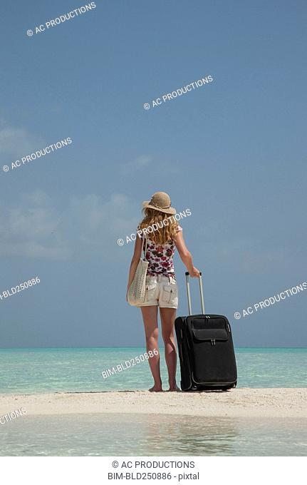 Caucasian woman holding suitcase on ocean beach
