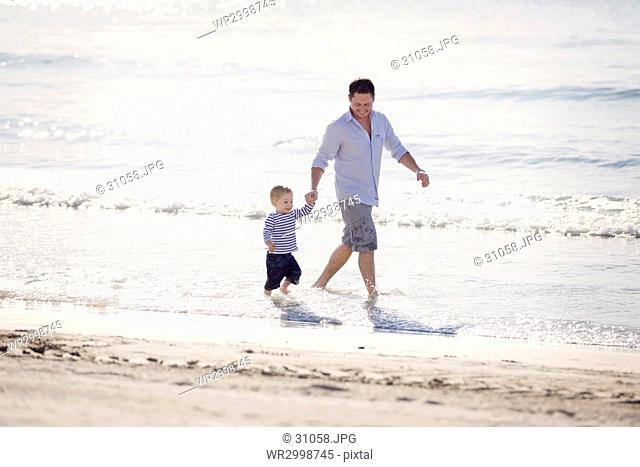 Man wearing shorts holding hands with young boy, walking in the ocean