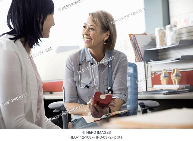 Doctor showing anatomical model to patient in office