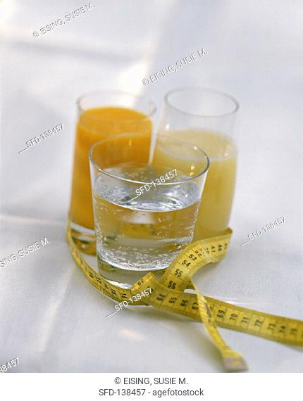 A glass of water & two glasses of juice, with tape measure