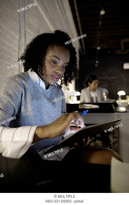 Focused businesswoman using digital tablet in dark office