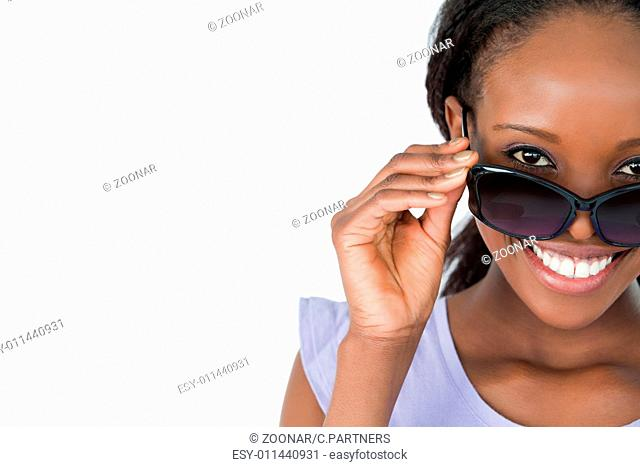 Close up of woman looking over her sunglasses on white backgroun