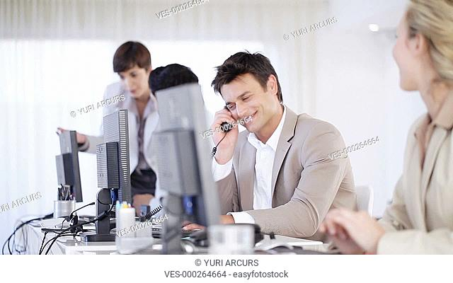 Friendly young businessman speaking on a telephone at his desk with his colleagues around him