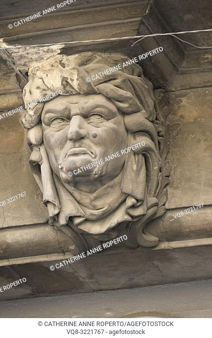 Eroded, frowning, draped male head corbel with down turned mouth and large moles seems to contemplate the broken, twisted power lines above him in old Avignon