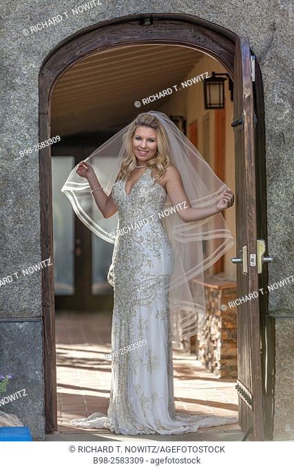 Bride standing in an arched doorway before her wedding