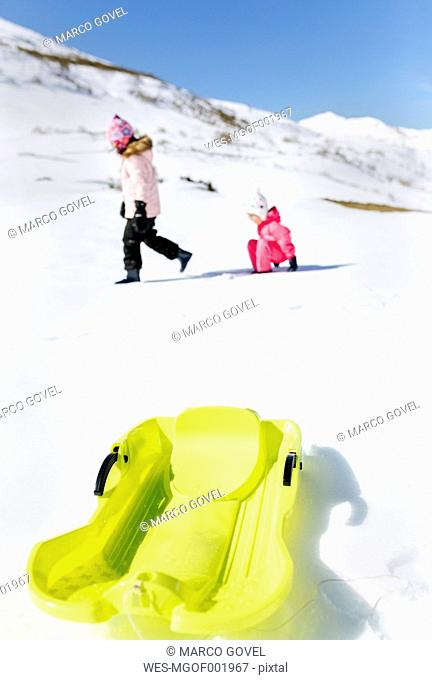 Spain, Asturias, kids playing in a snow, sledge in the foreground