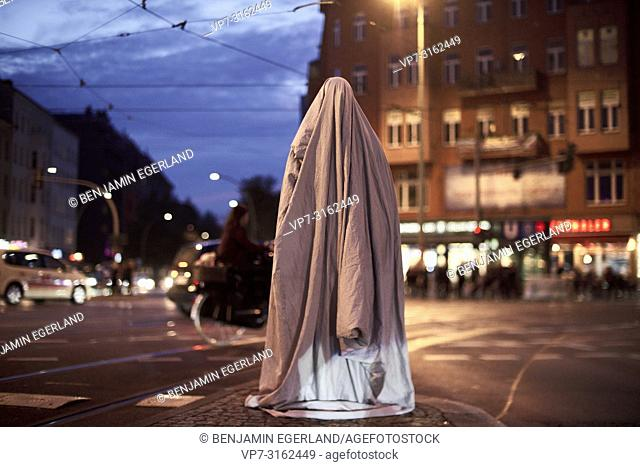 human under blanket standing on street in city Berlin, Germany