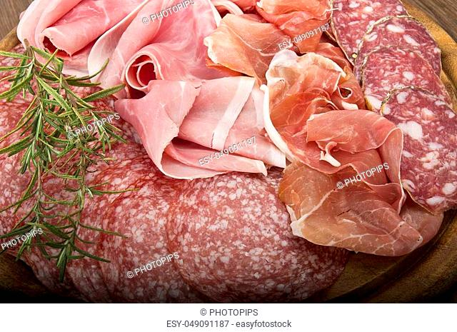 Wooden cutting board with various Italian salami