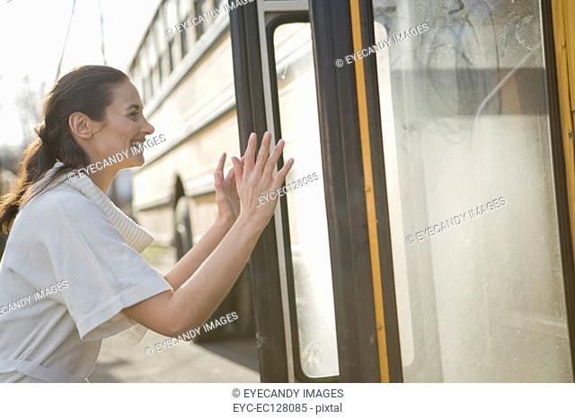 Side view of a cheerful young woman waiting by bus door