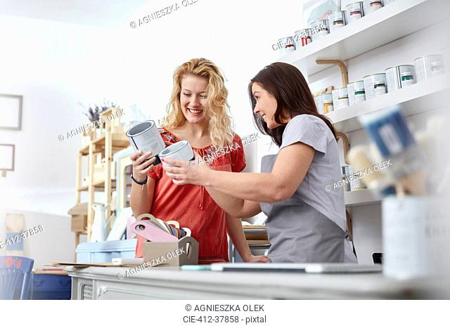 Smiling female business owner helping customer choose paint in art shop