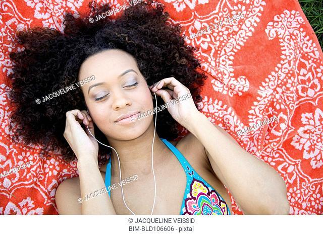 Hispanic woman laying on ground listening to music