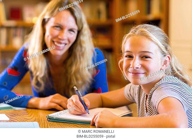 Portrait of Caucasian teacher helping student in library