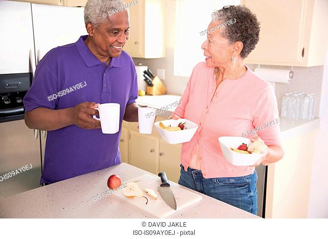 Senior couple in kitchen preparing breakfast
