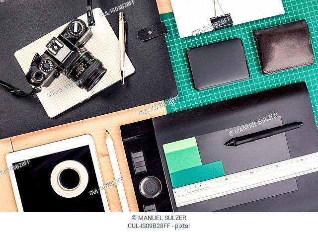 Overhead view of retro camera, notebook, diary, external hard drive, wallet, tripod and digital tablet