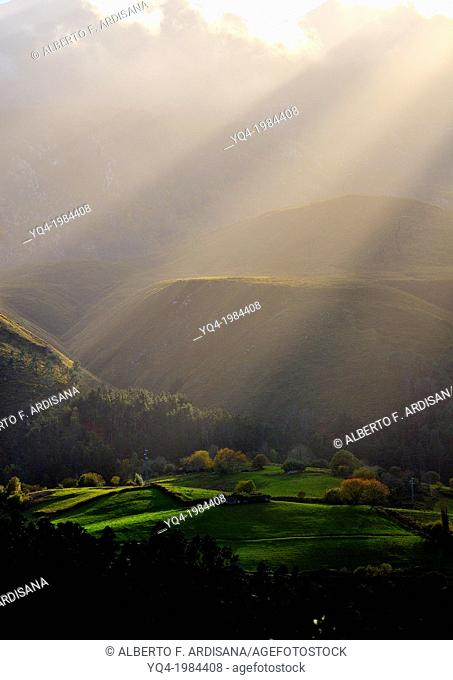 Light filters through the clouds, illuminating the valley of La Borbolla, in Llanes, Asturias, Spain