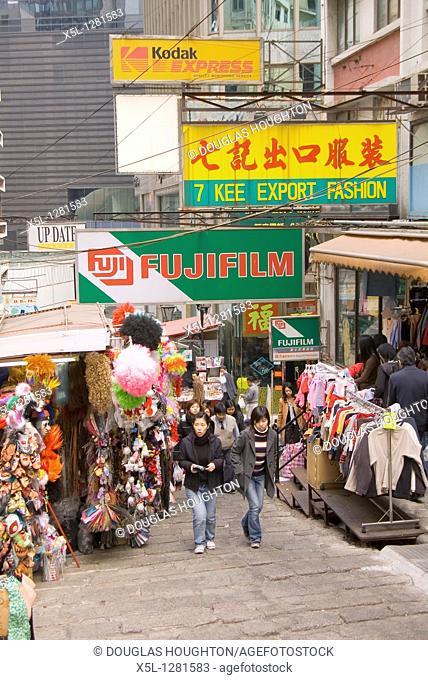 Pottinger Street CENTRAL HONG KONG Teenage girls walking up cloth stalls alley