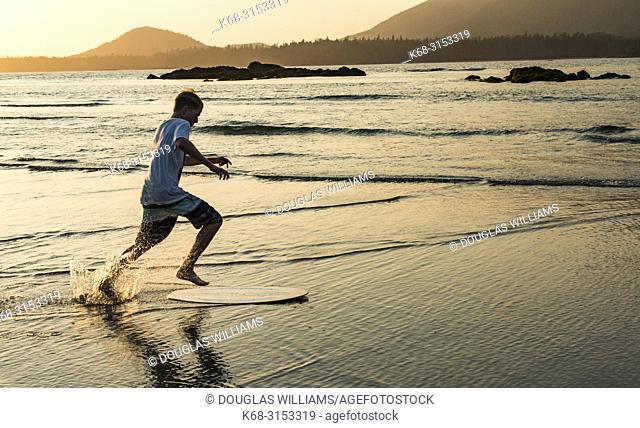 Teenage boy skim boarding on Flores Island, off the west coast of Vancouver Island, British Columbia, Canada