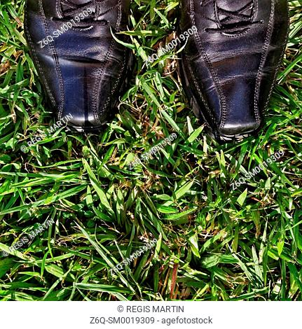 Man's business shoes in the grass
