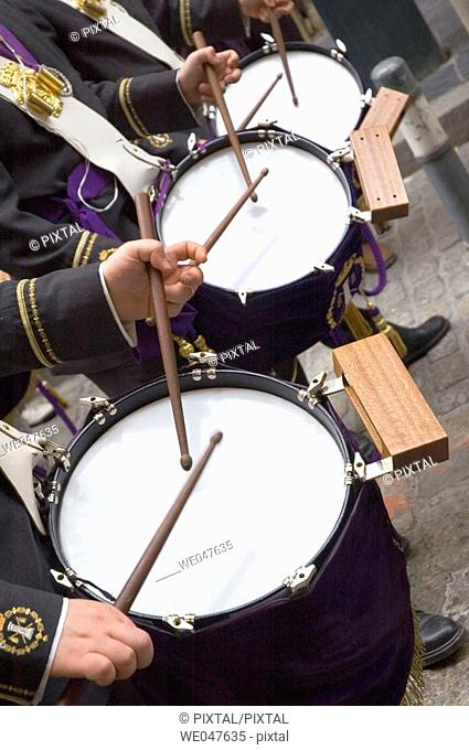 forefront of the hands of three musicians playing the drum