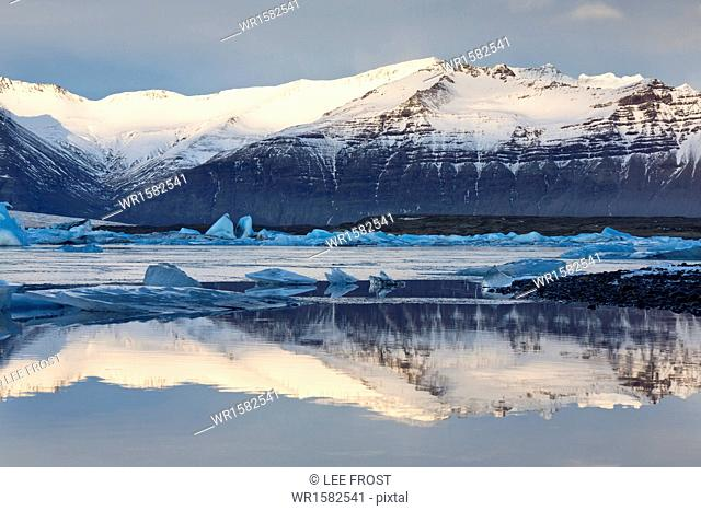 View over Jokulsarlon glacial lagoon towards snow-capped mountains and icebergs, with reflections in the calm water of the lagoon