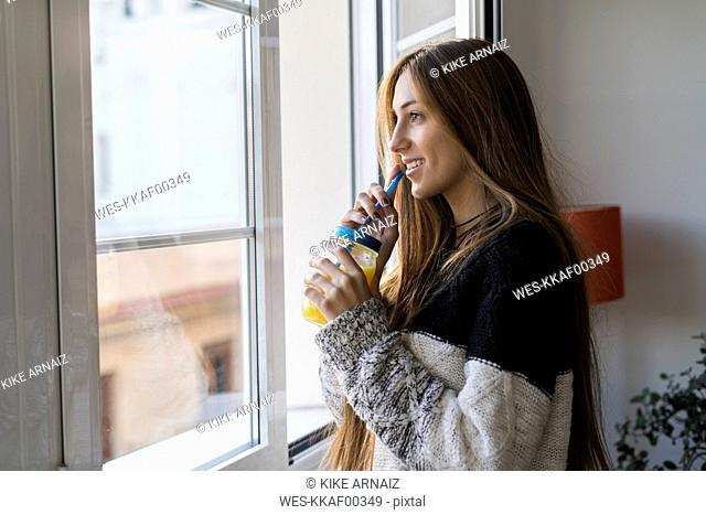 Young woman at the window drinking homemade drink