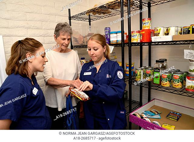 University of Arizona College of Nursing students review food labels with a Miracle Square resident at the pantry of the facility