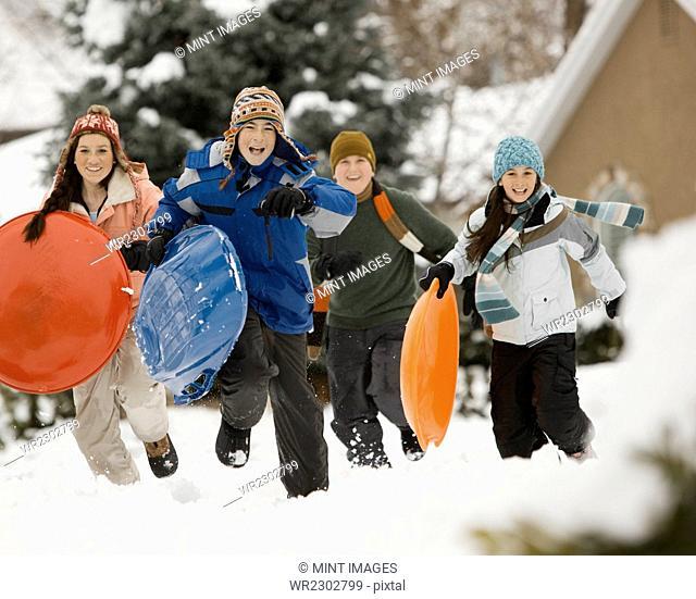 Winter snow. Four children, boys and girls, running across snow carrying sledges