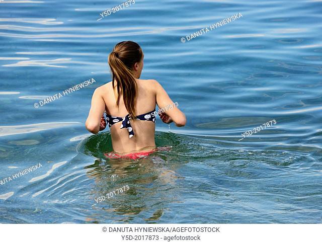 single one young woman entering water of Lake Geneva, Geneva, Switzerland