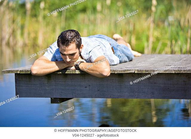 Young man on a footbridge at a lake contemplating