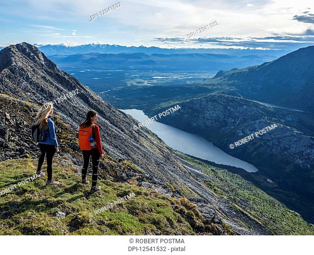 Two women exploring the mountains and wilderness of the Yukon. Feeling alive and vibrant in the beautiful scenery around Haines Junction; Yukon, Canada