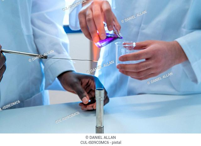 Young female and male scientists experimenting with liquid and bunsen burner in laboratory, cropped