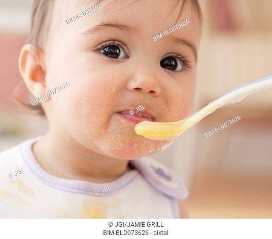 Mixed race baby girl eating