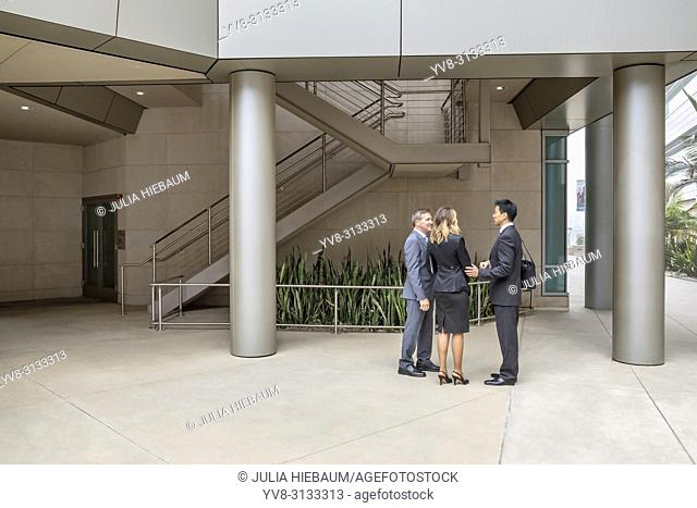 Three executives talking inside their office building