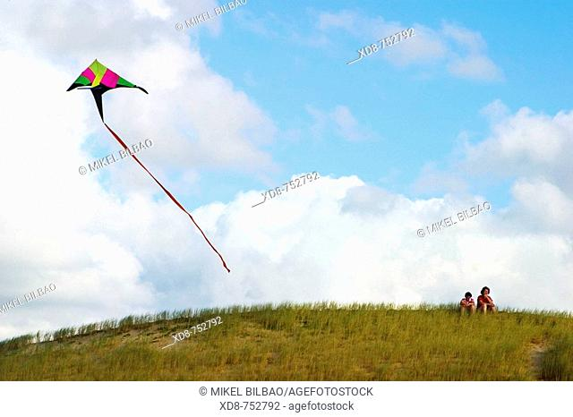 Kite flying in the sky over a hill with two persons, Somo, Cantabria, Spain