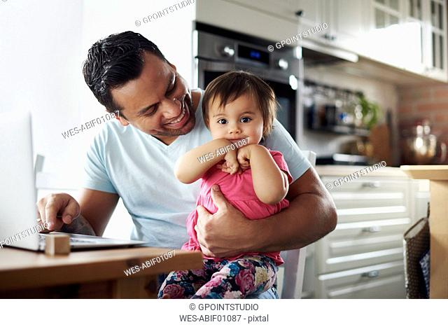 Smiling father with baby girl using laptop on table at home