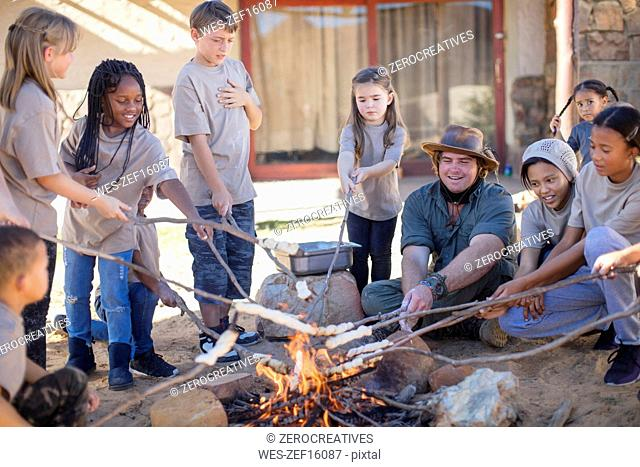 Children and guide roasting twist bread at camp fire