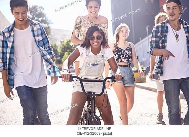 Teenage friends with BMX bicycle on sunny urban street