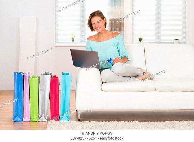 Woman On Sofa Shopping Online With Shopping Bags In Living Room