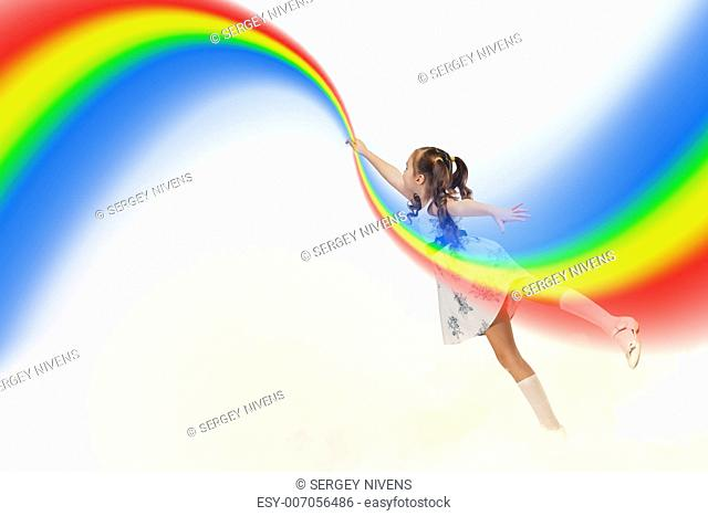 Image of little pretty girl drawing rainbow with finger