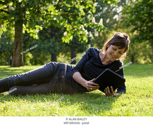 UK, London, Young woman sitting in park and using digital tablet