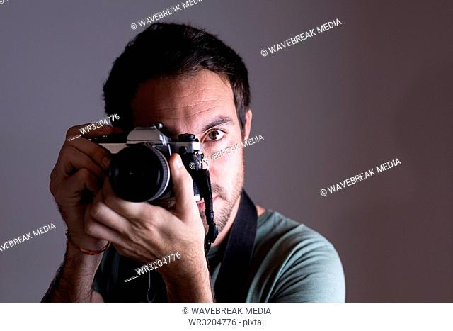 Male photographer clicking photos with camera