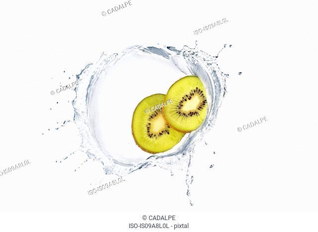 Two slices of kiwi splashing in liquid