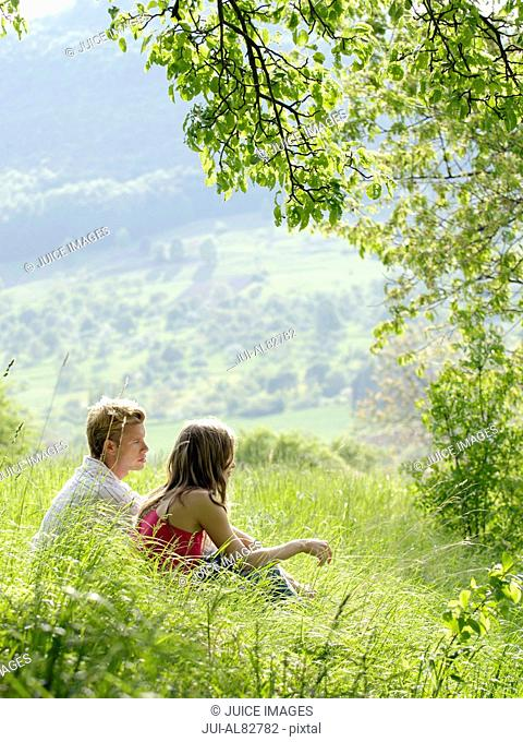 Couple sitting in grass on sunlit hillside