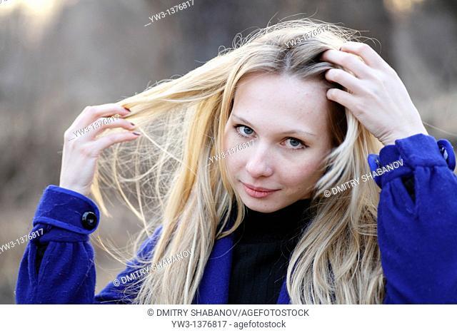 Portrait of beautiful woman in autumn in blue coat