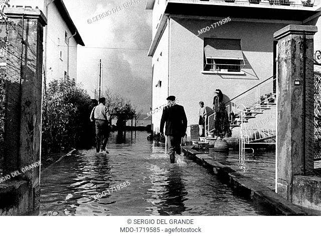 Flooded houses near the lake in Sirmione. Some Italian people walking among the flooded houses near the lake. Sirmione, November 1960