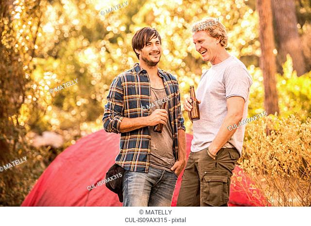Two male campers chatting and drinking beer in forest, Deer Park, Cape Town, South Africa