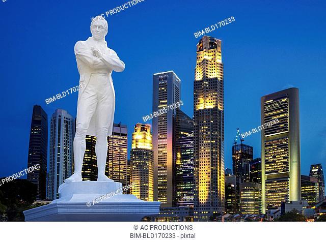 Statue and Singapore city skyline at night, Singapore, Singapore