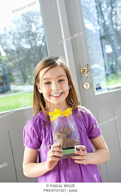 Portrait of a girl holding an Easter bunny and smiling