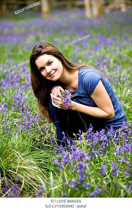 A young woman holding a bunch of bluebells