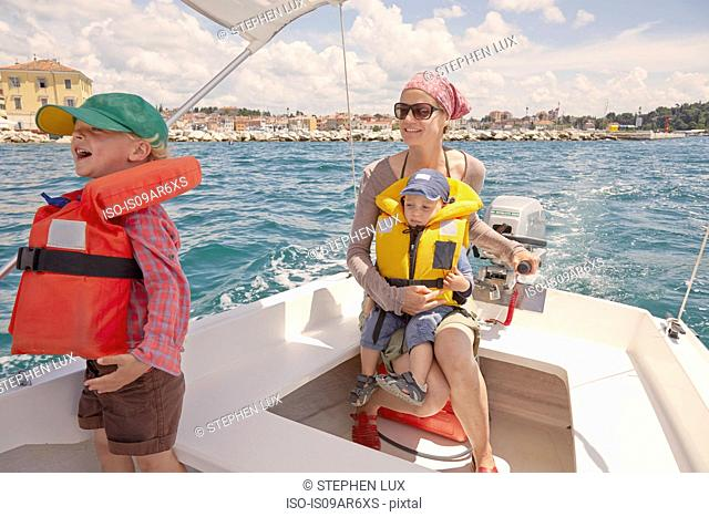 Mature woman with two boys steering motor boat, Rovinj, Istria Peninsula, Croatia
